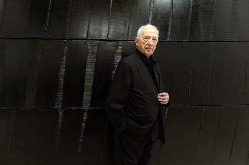 Pierre Soulages posant devant une de ses œuvres